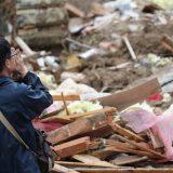【西日本豪雨被害】大規模な土砂崩れが発生した住宅地で、搬送される遺体に向かって手を合わせる男性=2018年7月8日午後、広島県熊野町川角 写真提供:産経新聞社