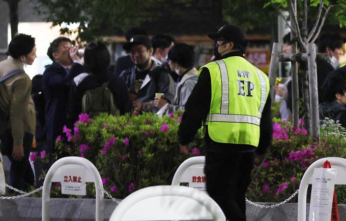 多くの人が集まった新橋駅近くの公園では、警備員(左手前)が密を避けるよう呼び掛けていた=2021年4月16日午後8時24分、東京都港区 写真提供:時事通信社