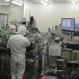 JAXAのクリーンルームがガラス越しに公開された チャンバーに手を入れる作業員(右側には粒子が2粒写っている)