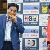 首に掛けられた後藤希友(右)の金メダルをかじる河村たかし名古屋市長=2021年8月4日午前、同市役所