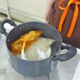 皿を敷き、お湯を張った鍋に食材の入ったポリ袋を入れる